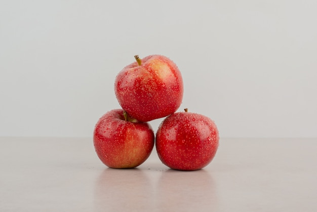 Rote, frische äpfel auf weißem tisch.