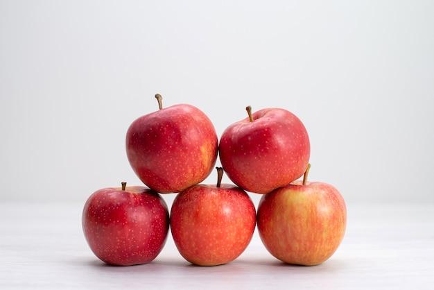 Rote frische äpfel der vorderansicht, die auf frische reife baumpflanze der weißen schreibtischfrucht ausgekleidet sind