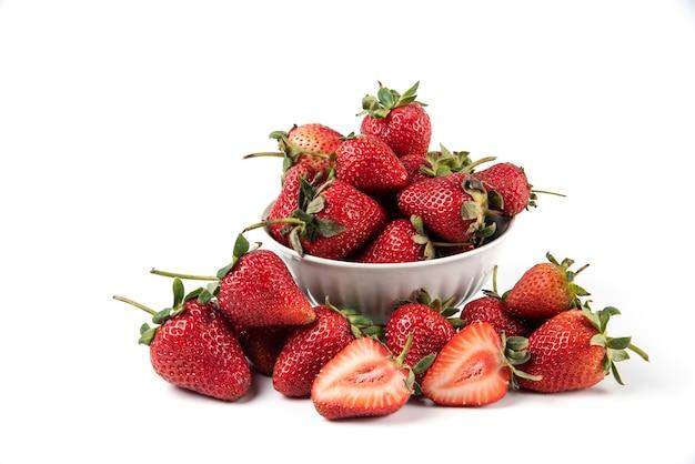 Rote frische erdbeeren mit grünen blättern in der weißen untertasse
