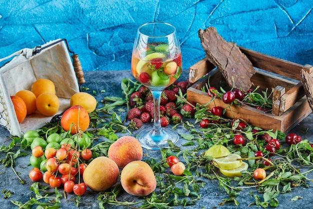 Rote frische kirschen auf holzkiste mit einem glas fruchtsaft und frischen früchten