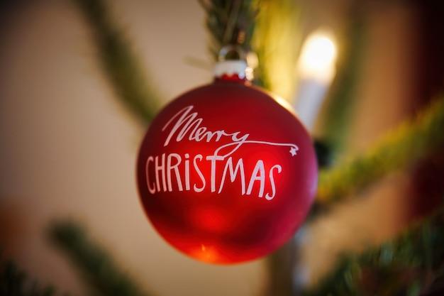 Rote frohe weihnachtskugel, die vom weihnachtsbaum hängt