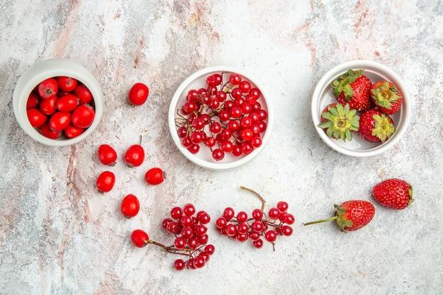 Rote früchte der draufsicht mit beeren auf frischer roter fruchtbeere des weißen tisches