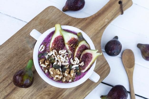 Rote früchte smoothie mit feigen müsli und nüssen gesunde und vegane bowl zum frühstück
