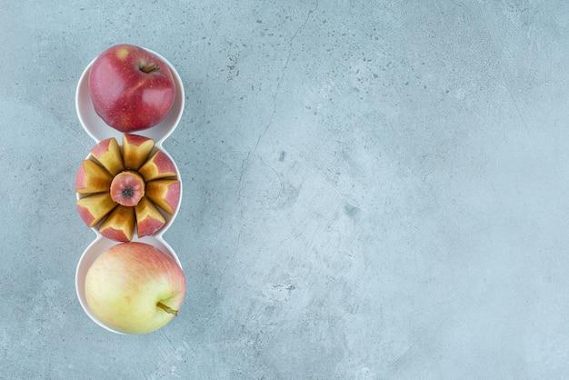 Rote ganze und geschnittene äpfel in weißen tassen.