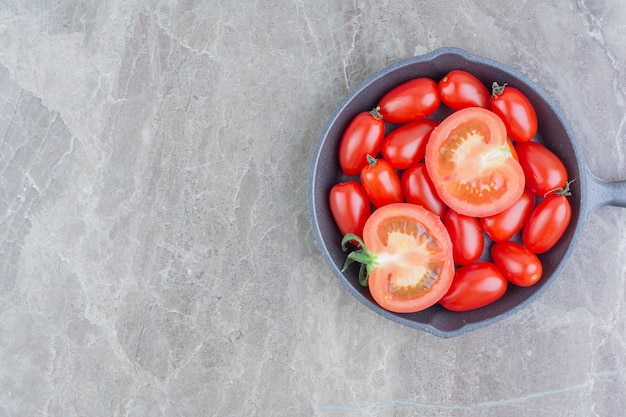 Rote ganze und halb geschnittene kirschtomaten in einer schwarzen pfanne