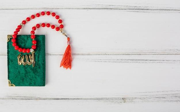 Rote gebetsperlen auf islamischem heiligem buch kuran der grünen abdeckung auf weißem schreibtisch