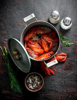 Rote gekochte krebse in einer pfanne mit gewürzen und dill auf dunklem rustikalem tisch.