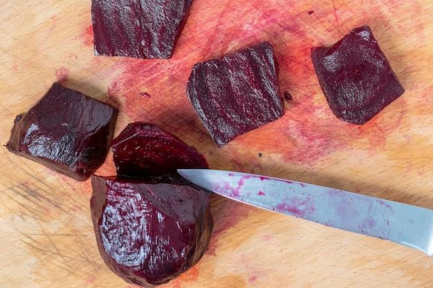 Rote gekochte rüben und messer auf dem schneidebrett in der küche, nahaufnahme, ansicht von oben