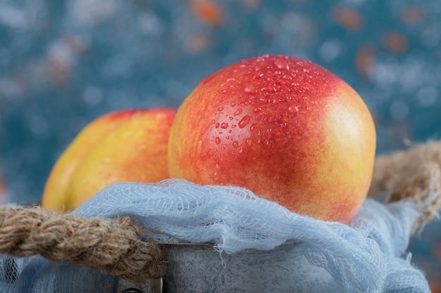 Rote gelbe pfirsiche in einem blauen metallischen eimer.
