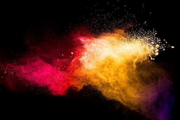 Rote gelbe pulverexplosionswolke auf schwarzem hintergrund. gefrierbewegung von rotgelben staubpartikeln spritzen.