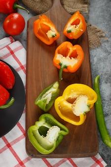 Rote, gelbe und grüne paprika auf einem holzbrett. draufsicht.