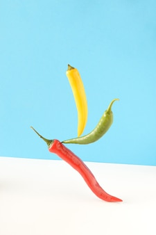 Rote, gelbe und grüne peperoni auf einer kombination aus blauem und weißem hintergrund. konzept der lebensmittelgravitation