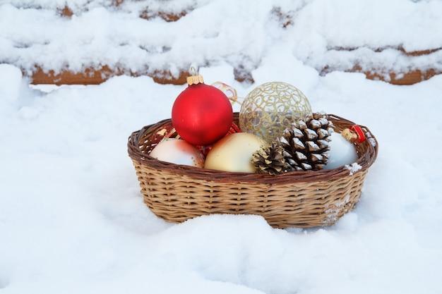 Rote, gelbe und weiße weihnachtskugeln in weidenkorb und holzbank mit schnee bedeckt auf dem hintergrund im winterstadtpark. weihnachts- oder neujahrskomposition.