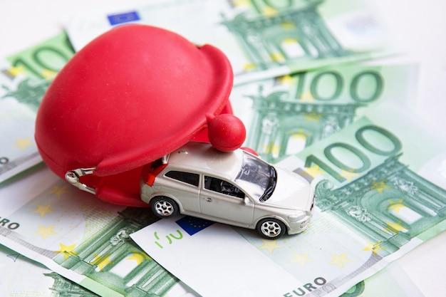 Rote geldbörse, spielzeugauto auf euro