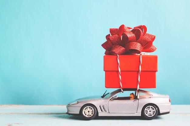 Rote geschenkbox auf autospielzeug mit blauem pastellfarbhintergrund, retro- filtereffekt