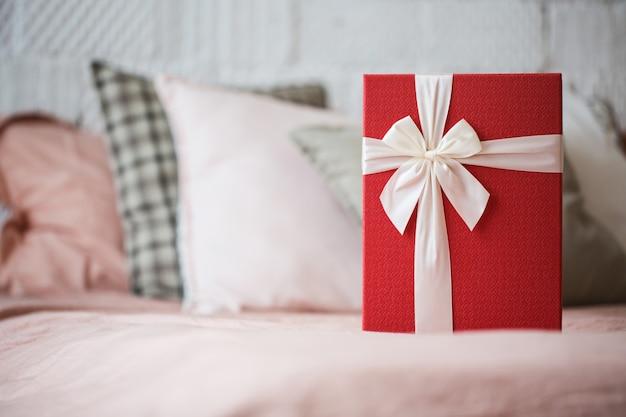 Rote geschenkbox auf dem bett.