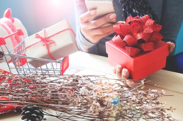 Rote geschenkbox auf frauenhand, unter verwendung des handys. ferienkonzept