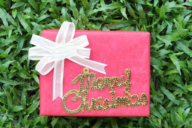 Rote geschenkbox auf grünem rasen- und goldtext von frohen weihnachten.