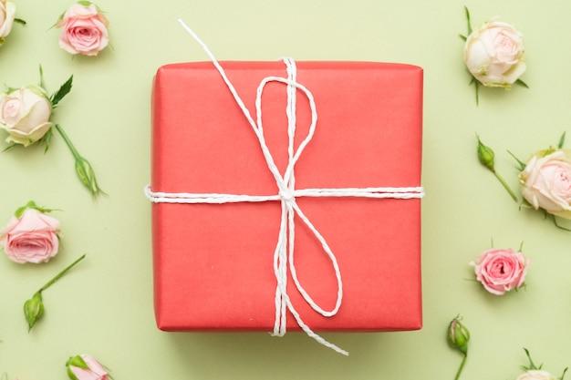 Rote geschenkbox auf grünem tisch. minimaler rosenranddekor. flach liegen.