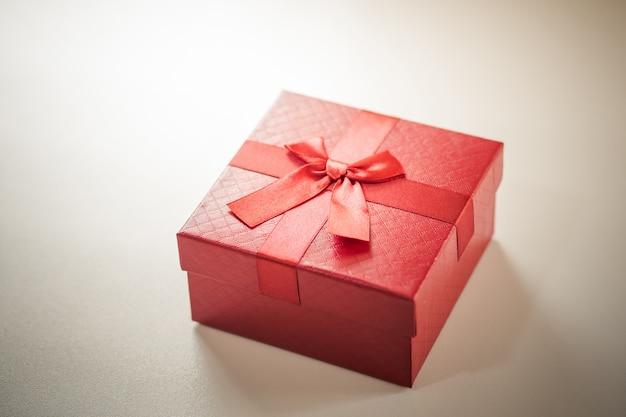 Rote geschenkbox auf hölzerner planke.