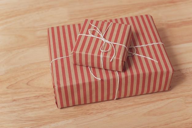 Rote geschenkbox auf hölzerner tabelle für weihnachten und guten rutsch ins neue jahr.