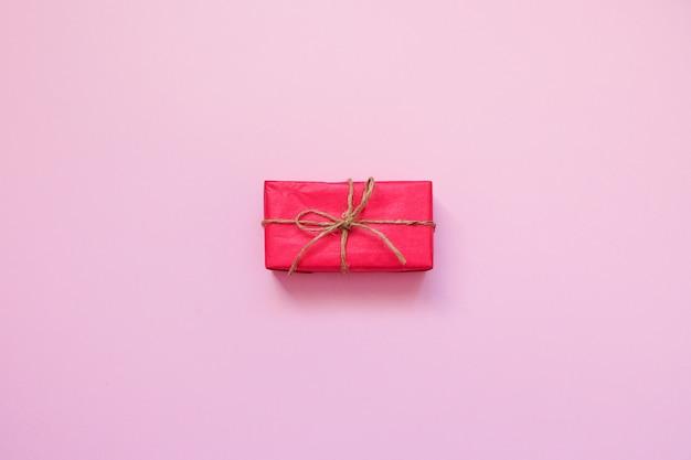 Rote geschenkbox auf rosa hintergrund.