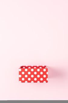Rote geschenkbox auf rosa oberfläche.