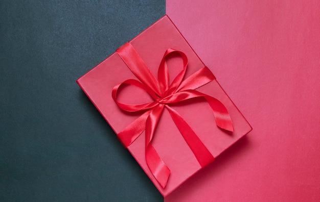 Rote geschenkbox auf rot-schwarzem hintergrund mit rotem band - grußkonzept