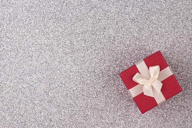 Rote geschenkbox auf silbernem hellem hintergrund