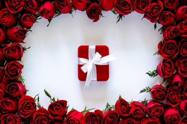 Rote geschenkbox auf weißem hintergrund mit rosenrahmen für jubiläums- und valentinstagkonzept.