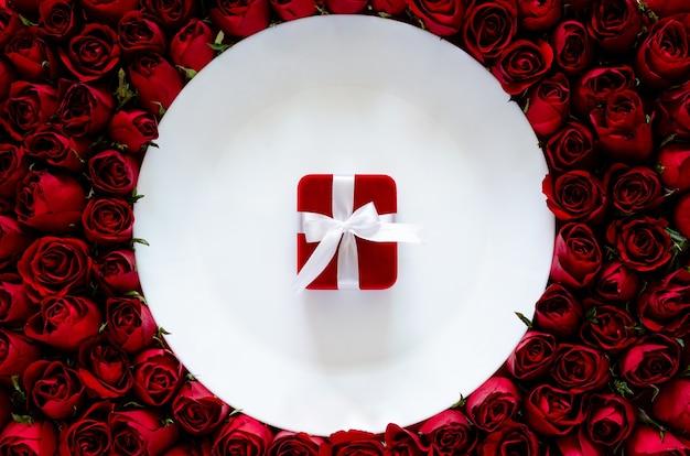 Rote geschenkbox auf weißem teller mit rosenhintergrund für das abendessen am jahrestags- oder valentinstagkonzept.