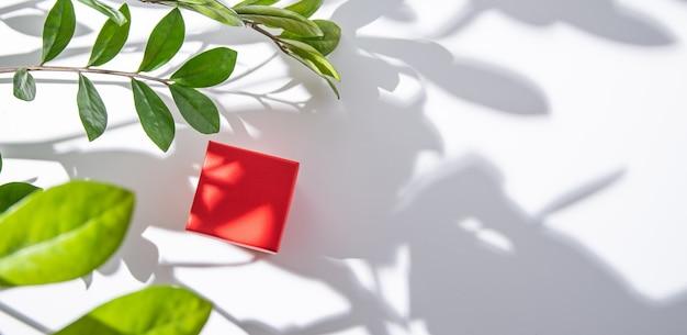 Rote geschenkbox auf weißem tisch unter frühlingsblumen mit morgenschatten