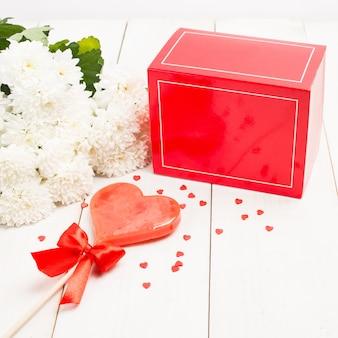 Rote geschenkbox, blumen und süßer herzlutscher