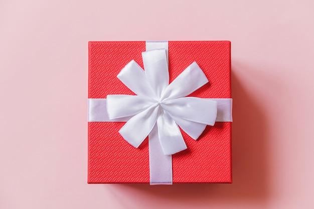 Rote geschenkbox des einfachen minimalen entwurfs lokalisiert auf buntem hintergrund des pastellrosas