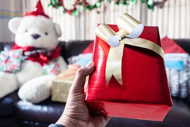 Rote geschenkbox in der hand zum geben am weihnachtstag
