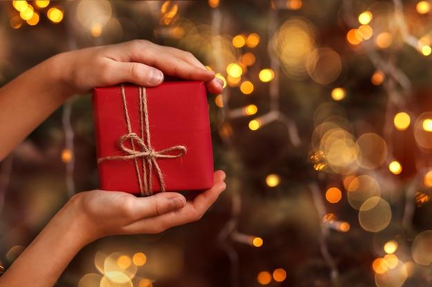 Rote geschenkbox in kinderhänden auf dem hintergrund eines weihnachtsbaumes mit leichten girlanden