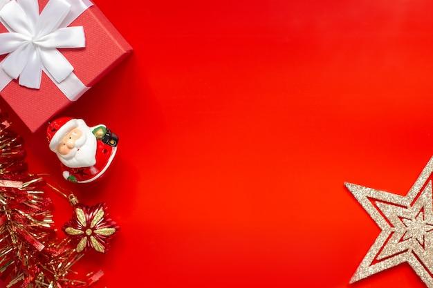 Rote geschenkbox, lametta, figur des weihnachtsmannes mit weihnachtsschmuck in form von goldenen sternen auf roter, flacher lage