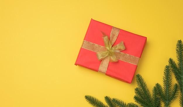 Rote geschenkbox mit band auf grauem hintergrund gebunden, ansicht von oben. festliche kulisse