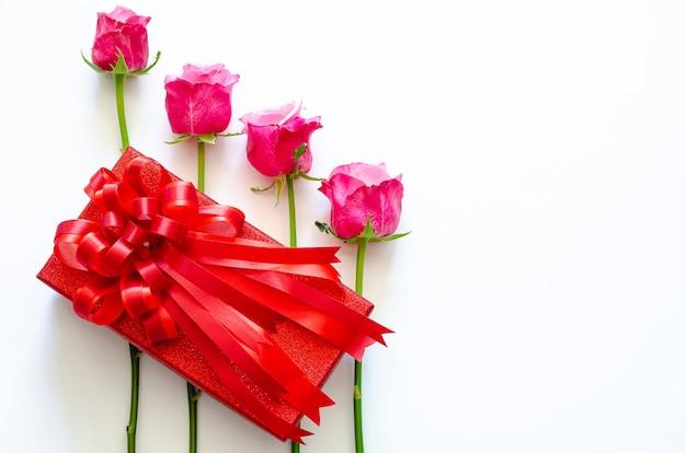 Rote geschenkbox mit band und rosa rosen auf weißem hintergrund für jubiläums- oder valentinstagkonzept.