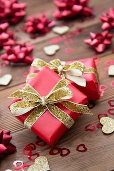 Rote geschenkbox mit bögen, auf holztisch. kopieren sie platz. valentinstag, geburtstag, weihnachten.