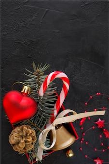 Rote geschenkbox mit einem weihnachtsspielzeug in form eines herzens, der tannenzweige, der weihnachtssüßigkeit, der girlande und der karte für glückwunschtext auf dem schwarzen hintergrund