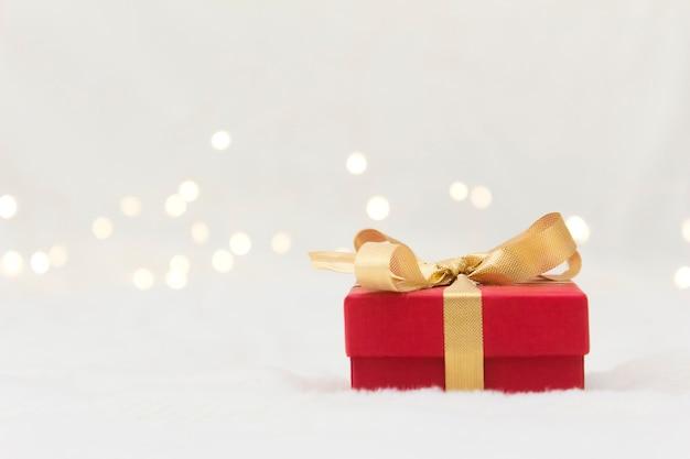 Rote geschenkbox mit einer goldenen schleife auf einem hellen hintergrund