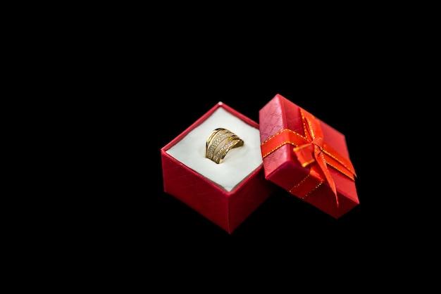Rote geschenkbox mit goldenem ring auf schwarzem hintergrund