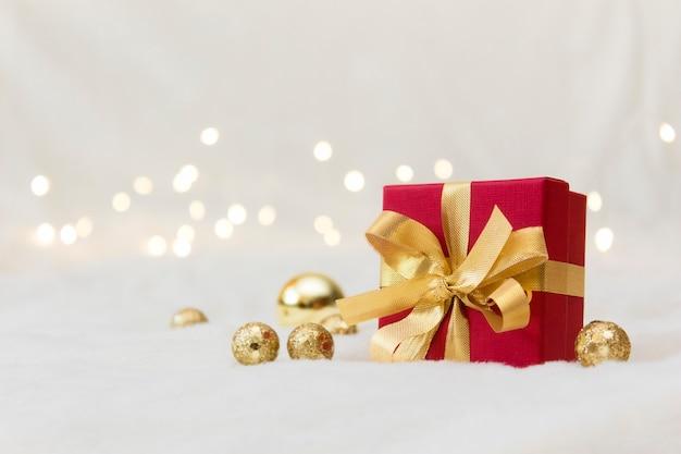 Rote geschenkbox mit goldener schleife