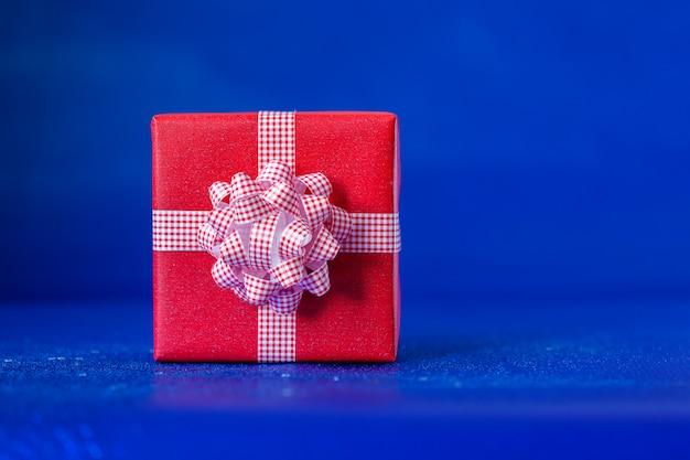 Rote geschenkbox mit großem bogen für geburtstag oder weihnachten. festliches konzept.