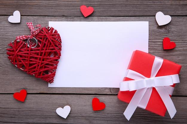 Rote geschenkbox mit herzen auf grauem hintergrund