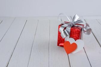 Rote Geschenkbox mit Herzform auf weißem Holztisch