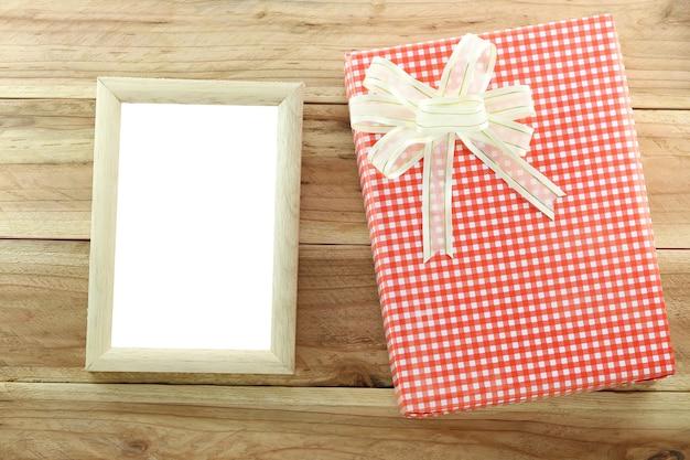 Rote geschenkbox mit leerem hölzernem bilderrahmen auf hölzernem hintergrund.