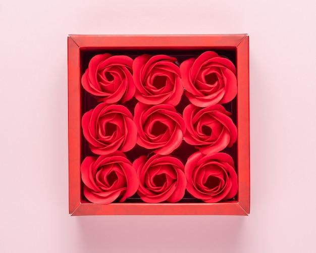 Rote geschenkbox mit rosenblüten auf rosa oberfläche.