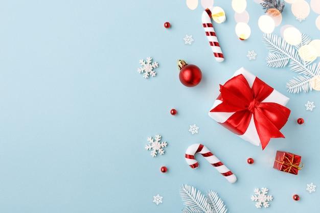 Rote geschenkbox mit weihnachtsdekorationen auf blauem hintergrund. draufsicht, flach liegen.